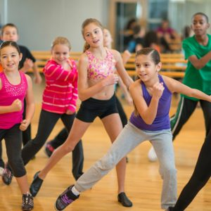 Diverse group of children taking a zumba dance fitness class